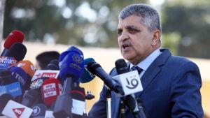Chefen för kanalmyndigheten vid Suezkanalen i Egypten talar på en presskonferens. Framför honom syns många mikrofoner.