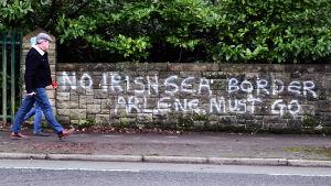 """Graffiti på en mur: """"NO IRISH SEA BORDER - ARLENE MUST GO""""."""