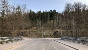 En vy från bron över Svartån mot Bruksvägen i Billnäs bruk. Mitt på bilden syns Banvallens motionsled. Asfalterad väg, skog, vår, bara lite grönska.