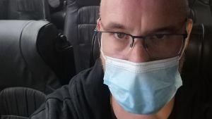 En man med munskydd sitter i en buss.