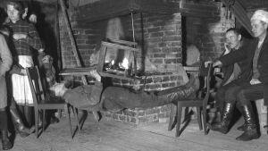 """En man leker """"ligga lik"""", där man håller kroppen så styv som möjligt och håller sig vågrätt mellan två stolar. Bilden är tagen 1935 i Bromarf."""