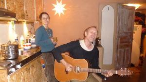 Charlie Jespergaard  spelar gitarr och sjunger. Bakom honom står Petra Blomqvist med en temugg i handen. De är hemma