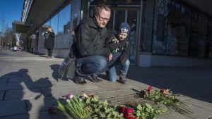 En man med sin son besöker platsen där Sveriges förre statsminister Olof Palme mördades för 30 år sedan.