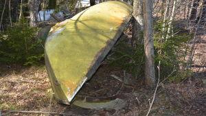 En övergiven, gammal båt i skogen.
