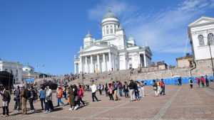 Folk på Senatstorget, i bakgrunden syns Helsingfors domkyrka.