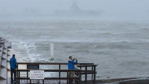 En person står på en brygga vid vattnet och fotograferar vågor i Corpus Christi, Texas, den 25 augusti 2017 samtidigt som orkanen Harvey närmar sig.