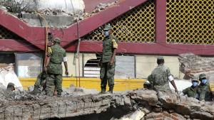 Mexikansk militär står bland ruiner av hus som rasat efter ett kraftigt jordskalv med magnituden 8,2 i Mexiko.