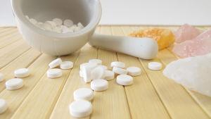 En mortel med vita tabletter, piller i. Rosenstenar, kvartsstenar syns också.