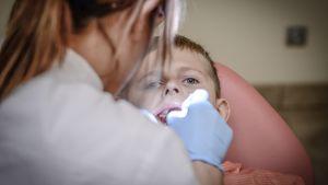 En tandläkare tittar in i munnen på ett barn