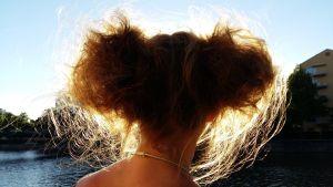 Kvällssolen lyser upp en flickas hår, som är format som Musse Pigg-öron.
