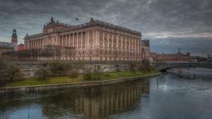 Sveriges riksdagshus med strömmen nedanför och mörka moln ovanför.