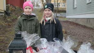 Flickorna Alicia Krook och Olivia Kraappa säljer bröd på julmarknaden i Pargas