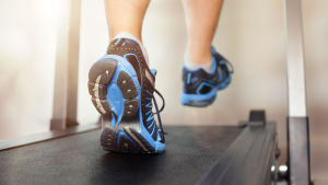 Närbild av fötterna på någon som springer på en löpmatta.
