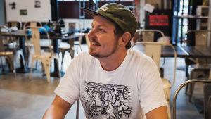 Mies eli Ossi Valpio valkoisessa t-paidassa vihreä lippalakki päässä katsoo hymyillen ohi kamerasta