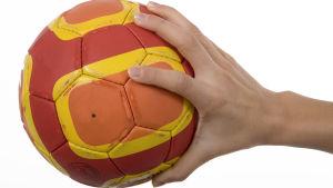 En hand håller i en handboll.