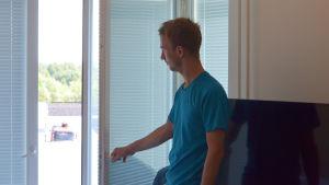 Jens Nyström öppnar ett fönster.