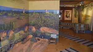 bild från inne i naturum med en väggmålning på träd och stenar och en liten brygga i bakgrunden