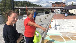 Stor karta över Borgå målad på asfalt som beundras av två personer.