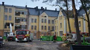 Brandbilar och brandmän framför en gammal gul stenbyggnad i centrum Åbo.