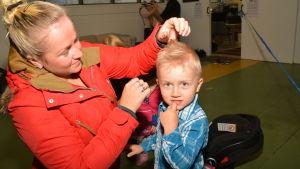 Moster Sabine Grönroos hjälper systersonen Hampus med håret inför daghemsfotografering.