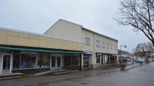 Vy över Köpmansgatan i Pargas under senhösten. Gula Tarmolahuset till höger, vita Pargas Affär-fastigheten till höger.