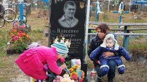 Ukrainsk familj vid siin stupade fars grav