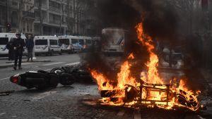 En motorcykel brinner på Boulevard de Courcelles i Paris. Demonstranterna har tänt många små bränder under dagens lopp.