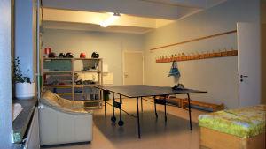 En trång aula i en skola där en beige lädersoffa står invid ett pingisbord. Till höger syns en vit dörr som står öppen.