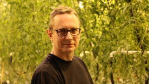 En man med glasögon och kort ljust hår står intill tomatplantor i ett växthus.