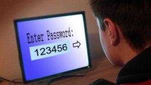 Näytöllä salasana: 123456, poika katselee näyttöä, kuvattu takaviistosta