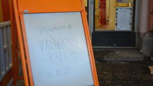 """En orange skylt med texten """"Välkommen på vänskapskafé kl. 18-20"""""""