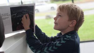 Sunes lillebror Håkan bläddrar i en bilbroschyr.