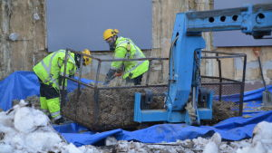 Byggnadsarbetare med gasmasker som arbetar med isoleringsmaterial