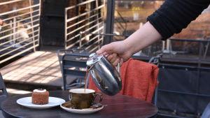 Kaffe hälls upp i en kopp bredvid en runebergstårta