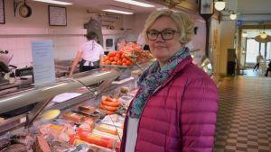 En kvinna står mitt i bild framför en köttdisk.