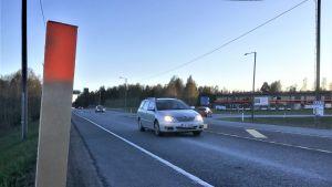 En T-korsning där personbilar kör åt olika håll. Affärsbyggnader syns i bakgrunden. Asfalterad väg, skymning.