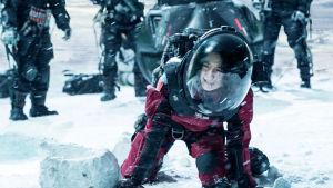 Närbild på Han Duoduo (Jin Mai Jaho) på knä i snön iklädd rymddräkt.