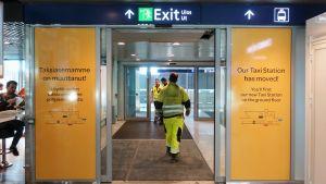 """Byggarbetare går med ryggen vänd mot kameran ut från Helsingfors-Vanda flygplats. På sidan av skjutdörrarna står texten """"Taxistationen har flyttat!"""""""