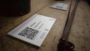 En lapp med en pixlad qr-kod för mobiler på ett gammalt träbord.