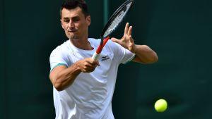 Bernard Tomic slår en tennisboll.