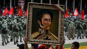 Publiken bar fram ett porträtt på nationalhjälten Simon Bolivar under fredagens militärparad i Caracas.