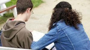 En bild på två personer som läser från ett papper. Vi ser bara personernas ryggar - den ena är en kvinna med lockigt hår och den andra en man