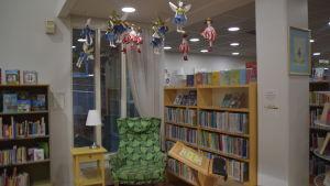 En länstol och ett litet bord med bordslampa i ett bibliotek. Läshörna. I taket hänger tygdockor som ser ut som älvor.