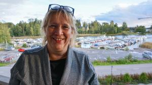 Kvinna i grått, bakom syns småbåtshamn i Gumbostrand