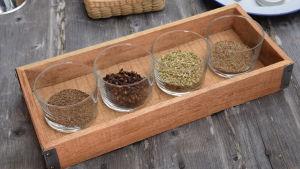 En avlång träbricka med fyra låga glas. I glasen finns olika kryddor som kummin, fänkål, kryddnejlika och anis.