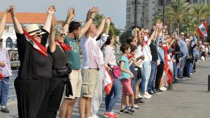 Libaneser formar människokedja genom att hålla varandra i händerna.