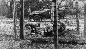 En svartvit bild från 1960-talet. Bilden är ganska grynig men man ser att fyra uniformsklädda män sitter i huk vid något på marken. Mellan dem o fotografen finns taggtråd och i bakgrunden en pansarvagn.