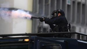 Mellakkavarusteinen poliisi ampuu kyynelkaasua.