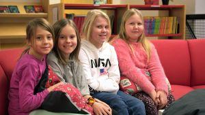 Matilda Sandgren, Isa Sundell, Lydia Norrgrann och Aura Lindgren sitter på en röd soffa.