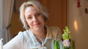 En kvinna vid ett köksbord. Man kan se lite av en julhyacint. Hon tittar in i kameran och ler lite.